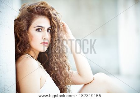 Beautiful and attractive young woman sitting. Long curly hair. Leaning on a white wall. Sitting on the ground. Sensual and radiant beauty.