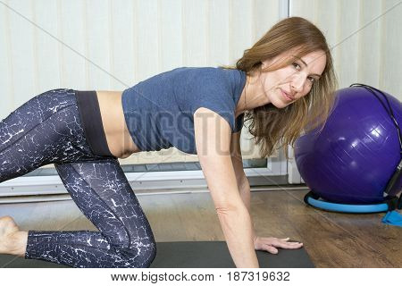 Home Fitness. Portrait of beautiful young model working out in home interior.