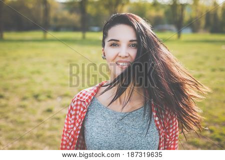 Portrait of pretty hipster girl outdoors. Looking at camera. Positive human emotion facial expression body language, concept of funny girl