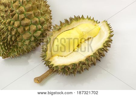 Durian on a white plate with green spikes rind and yellow background king of the fruit but smelly in Thailand and south east asia; soft focus