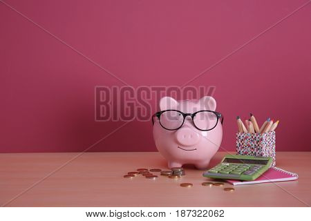 Piggy bank with spectacles, coins, calculator and stationery on color background