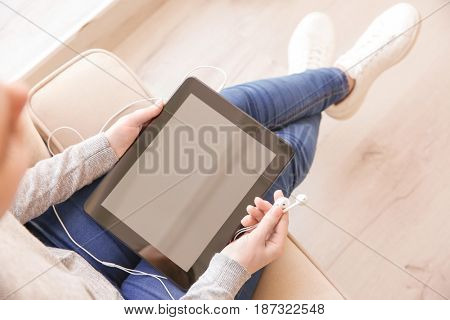 Audio book concept. Young woman holding tablet and earphones, close up