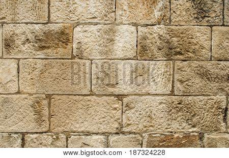 Old sandstone blocks stonewall closeup as background