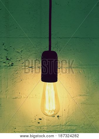 Simple light bulb on a black cord. Design with retro feel.