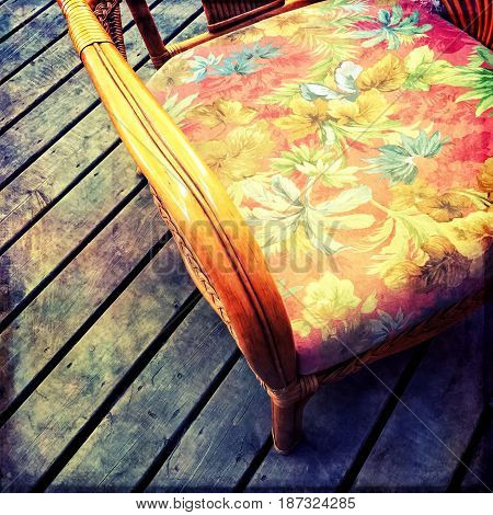 Vintage armchair with floral design on a dark wooden floor.