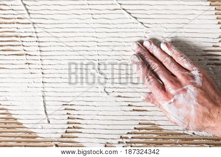 Unrecognizable builder work with stucco. Dirty worker hand on white rough plastered surface, flat lay. Relief background with free space.