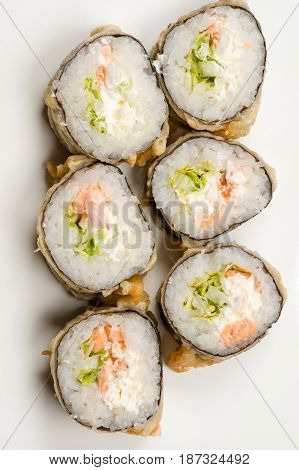 six delicious sushi rolls from above isolated on gray background