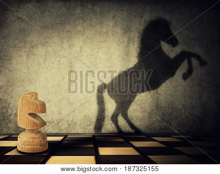 Magical transformation as a wooden knight chess piece casting a shadow of a wild horse on two legs on the wall. Symbol of business aspirations freedom and leadership concept.