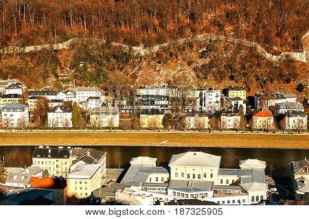 Beautiful views of traditional houses in a row next to the river at the foot of the mountain in the Austrian city of Salzburg. The fourth largest city in Austria, Europe. Mozart's homeland.
