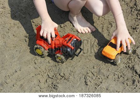 Child play near water. Child plays with toy cars on a wet beach.