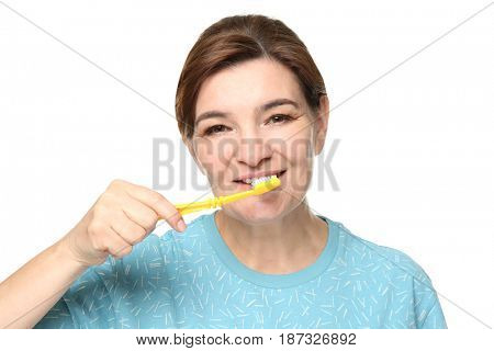 Senior woman cleaning teeth on white background