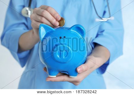Female doctor putting coin into piggy bank, close up. Concept of medical insurance