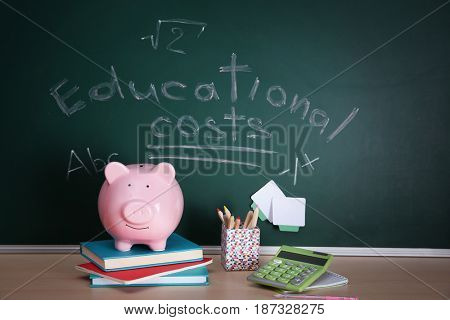 Piggy bank with stationery on chalkboard background. Education costs concept