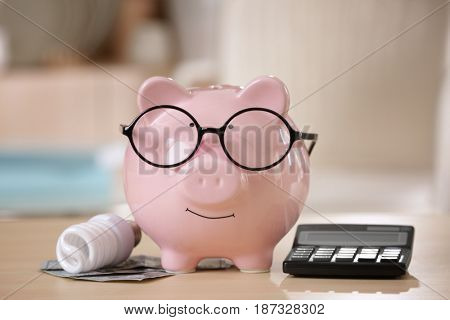 Saving electric power concept. Ceramic piggy bank with calculator and money on table