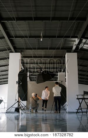Creative photo and video team shooting in studio interior. Professional photographers taking shots of male model. Fashion photosession backstage