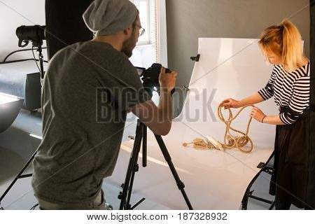 Creative team shooting still life. Back view of photographer taking object shots with assistant in studio interior. photoshoot backstage