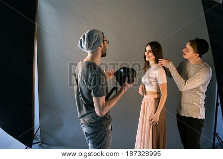 Creative fashion team work with model in studio. Professional stylist and photographer communicate with cheerful woman on photoshoot