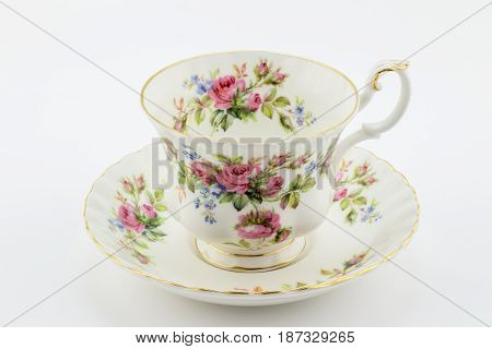 Empty antique cup and saucer with rose decoration isolated on white - English tea