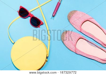 Colorful stylish female summer accessories collection on blue background, top view