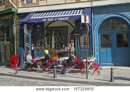 PARIS FRANCE - APRIL 2 2017: Tables on the sidewalk in front of a small cafe. The island of Cite a sunny day in early April. Paris France.