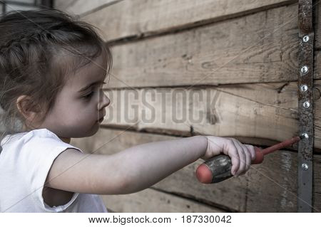 Little Girl With Screwdriver In Hands