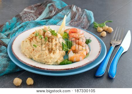Chickpea puree with cream and butter served with boiled prawns on a white and blue plate on a grey abstract background. Healthy food. Healthy eating concept