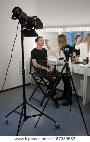 Vertical indoors shot of woman shooting beauty blog and putting makeup to man in professional salon.