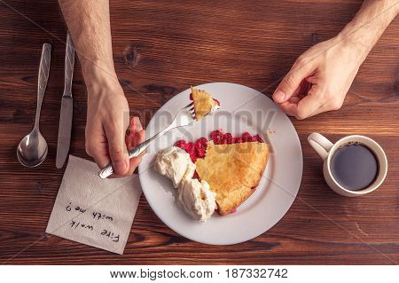 Fresh homemade pie with cherry pulp and ice cream on a plate. A slice of a cherry pie with a ruddy crust on a wooden table. Cherry pie and mug of delicious hot black coffee. Top view.