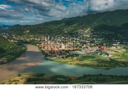 Mtskheta Georgia. Aerial View Of Picturesque Highlands With Blue Sky Over Ancient Town In Green Valley Of Confluence Of Two Rivers.