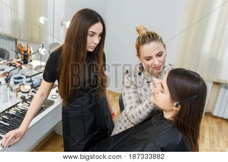 Makeup master class at beauty school. Professional make-up artist work in her studio. Visagiste applying makeup