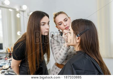 Makeup course at beauty school. Professional makeup artist conducts a master class. Make-up artist work in her studio. Real people. Visagiste applying makeup