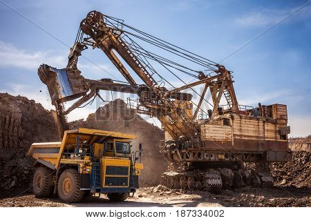 Excavator loading dump truck at coal mining