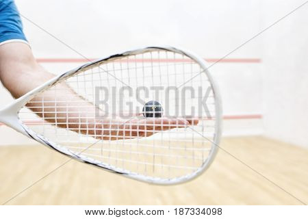 men's hands holding squash racket and ball. Racquetball equipment. Photo with selective focus. Player prepares to serve a squash ball. Closeup of male hand serving ball