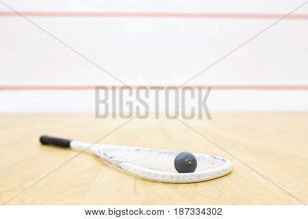 racket and ball for squash game. Racquetball equipment on the court and wall with red lines on the background. Photo with selective focus