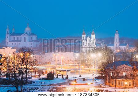 Vitebsk, Belarus. Evening Night View Cityscape With Famous Landmarks Is Assumption Cathedral, Church Of The Resurrection Of Christ Upper Church And Old Town Hall In Street Lights Illumination