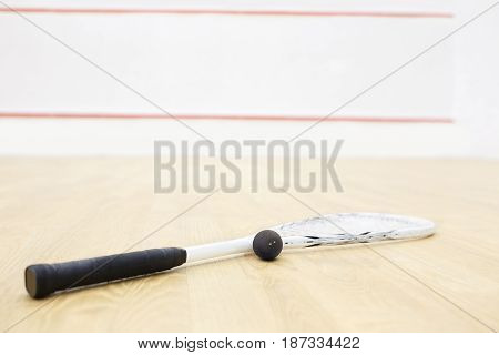 squash racket and ball. Racquetball equipment on the court and wall with red lines on the background. Photo with selective focus