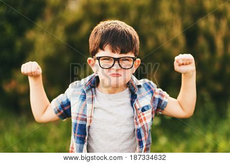 Strong and smart little boy with funny facial expression playing outdoors, wearing eyeglasses and blue plaid shirt