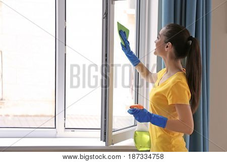 Young woman using detergent and rag while cleaning window in room