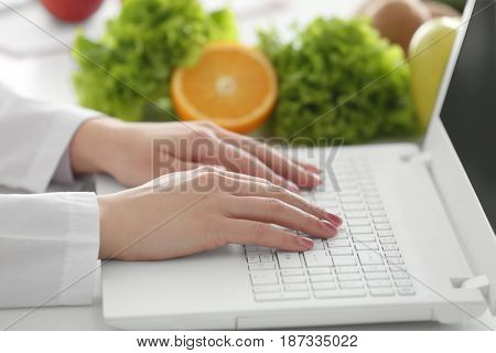 Young female nutritionist working on laptop in office, close up