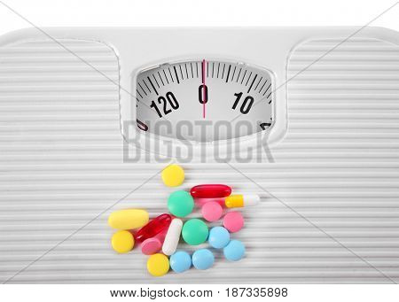 Diet concept. Heap of assorted pills and scales, closeup