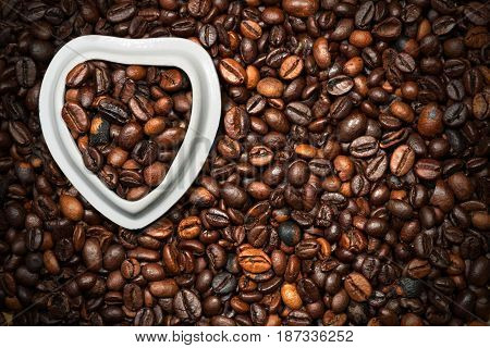 Roasted coffee beans in a heart shaped bowl on a background with many coffee beans. Love Coffee concept