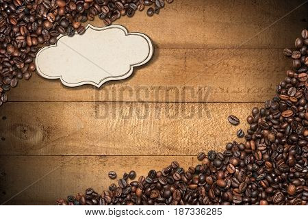 Group of roasted coffee beans on a wooden background with planks copy space and a blank label