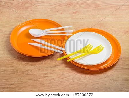 Orange and white disposable plastic plates different sizes plastic disposable yellow forks and white spoons and knives on a wooden surface