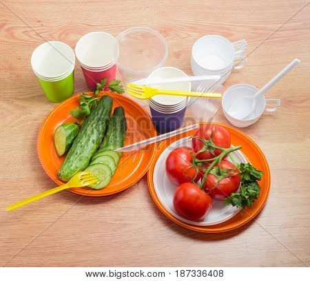 Different disposable plastic plates partly sliced cucumbers with fork and knife and cluster of the tomatoes on them paper and plastic disposable cups with spoons beside on a wooden surface