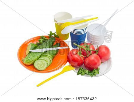 Orange and white disposable plastic plate with whole and sliced cucumber cluster of the tomatoes forks spoons and knifes paper and plastic disposable cups beside on a light background