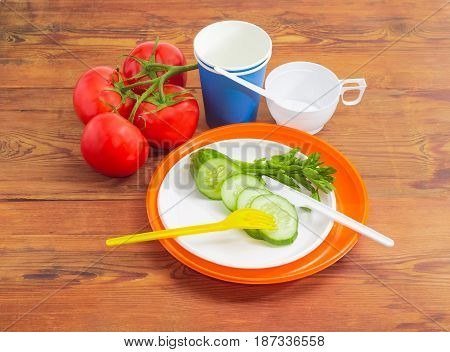Disposable plastic plates fork knife and sliced cucumber on it claster of the tomatoes paper and plastic disposable cups with spoons beside on a surface of the old wooden planks