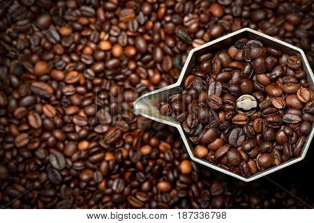 Closeup of an old italian coffee maker (moka pot - top view) with roasted coffee beans inside and on background