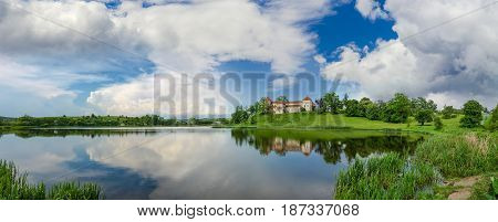 Panorama of pond after a thunderstorm with ancient castle on the opposite bank. Svirzh Castle built in the 15th century Lviv region Ukraine.