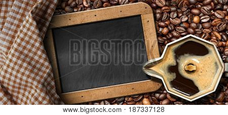 Old italian coffee maker (moka pot - top view) with roasted coffee beans on the background and an empty blackboard with copy space