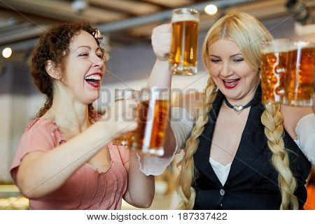 Two laughing women with glass mugs with beer.